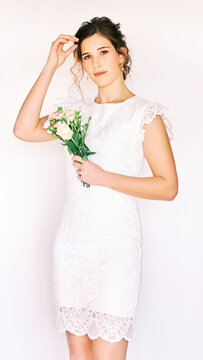 Portrait of young pretty woman wearing white dress, holding roses and carnation flowers