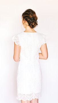 Portrait of young pretty woman wearing white dress, back view