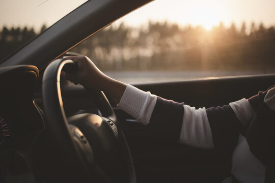 Driving car in sunset or sunrise, Closeup hand on steering wheel driving car in morning or evening
