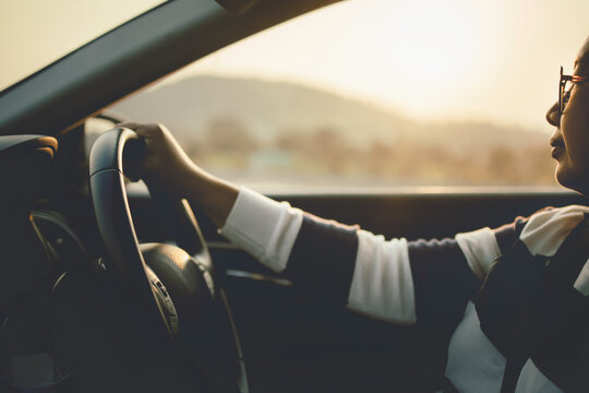 Driving car in sunset or sunrise, Asian woman in eyeglasses holding steering wheel driving car in morning or evening in countryside