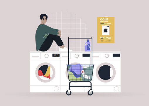 Household chores concept, a young male Asian character waiting for their laundry in a coin laundromat