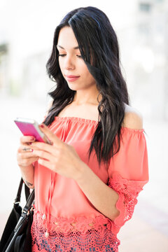 woman walking down the street in a city happy with her phone watching internet