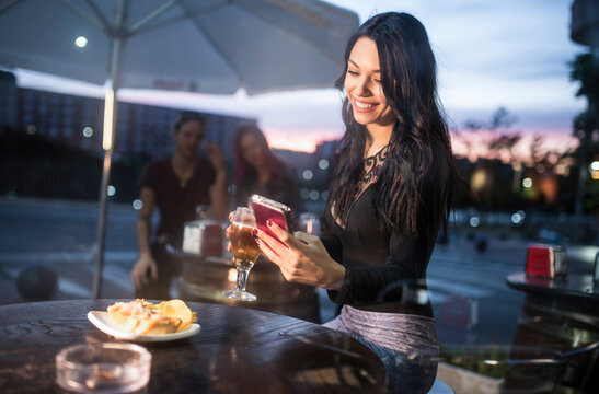 woman loking smartphone in bar terrace while drinking beer