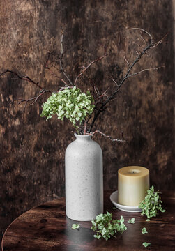 Home cozy still life - vase with dried hydrangea flowers and candle  on a wooden table
