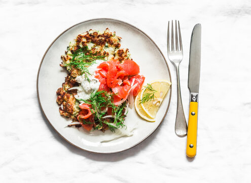 Cauliflower fritters with smoked salmon and greek yogurt sauce on a light background, top view