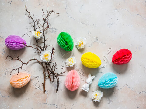 Easter decoration - tree branches, paper colored eggs, flowers, ceramic easter rabbit on a light background, top view. Handmade creativity concept