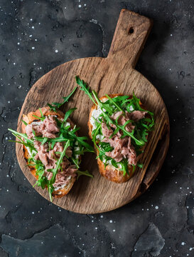 Snack sandwiches with canned tuna, cream cheese and arugula on a cutting board on a dark background, top view