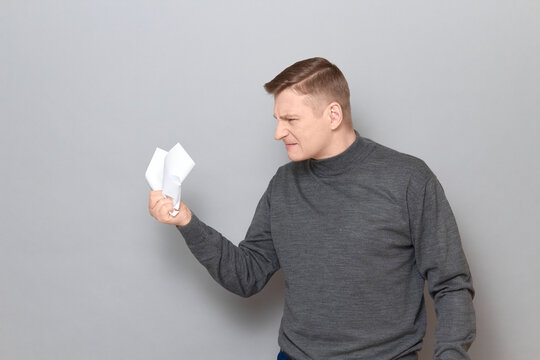 Portrait of angry furious mature man holding in hand crumple paper