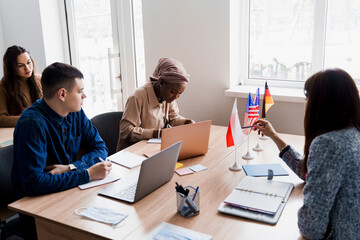 Multiethnic students and teacher study foreign languages together in class. Studing with laptop. Black handsome girl student study with white people together and look into camera