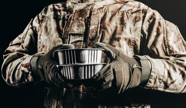 Photo of soldier in camouflaged uniform and tactical gloves holding canned food field ration on black background.