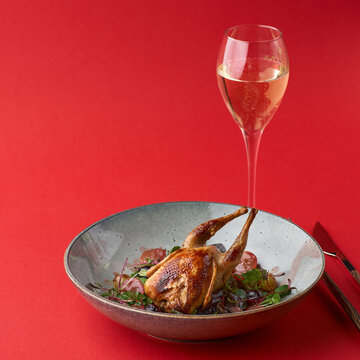 fried quail and fresh vegetables in a plate. red background, food for menu