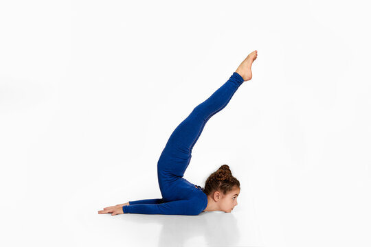 flexible child girl in blue sportswear performs gymnastic exercises on white studio background