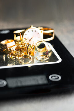Gold jewelry rings, chain,braclets, watch,  earrings on jewelry balance. We buy gold concept