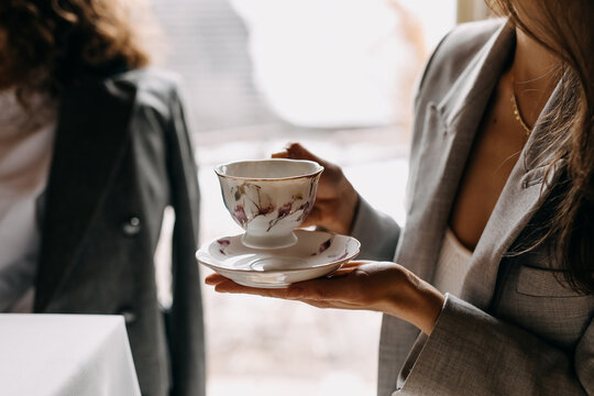 Woman holding a vintage porcelain cup of coffee with a small plate at breakfast in a restaurant.