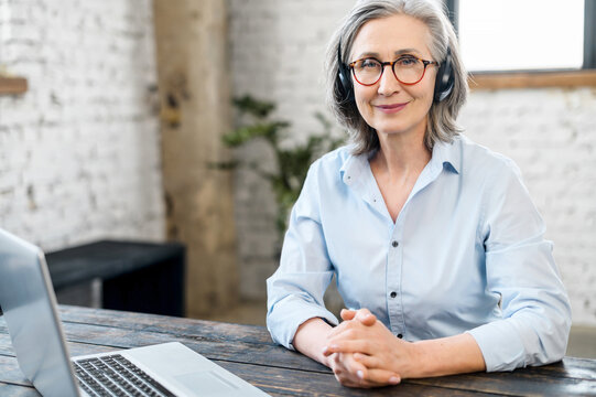 Mature senior office worker businesswoman with a pleasant smile in headset and glasses looking at the camera, sitting at the desk. Female call center operator is feeling motivated and ready to work