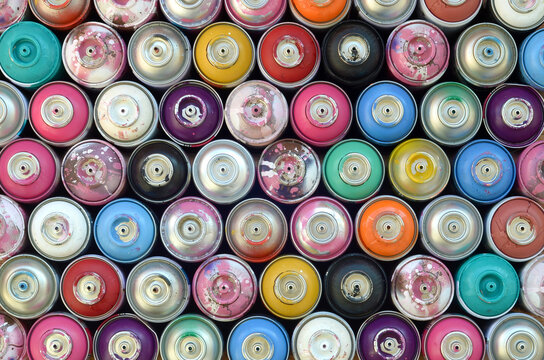 Large number of used colorful spray cans of aerosol paint lying on the treated wooden surface in the artist's graffiti workshop close up. Dirty and stained cans for art