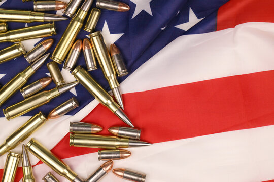 Many yellow 9mm and 5.56mm bullets and cartridges on United States flag. Concept of gun trafficking on USA territory or special ops