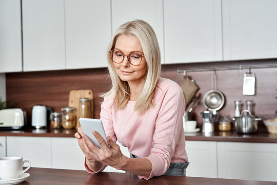 Middle aged 50 years old woman using apps ordering buying food on smartphone sitting in kitchen at home. Mature older lady holding mobile phone texting messages, browsing online services.