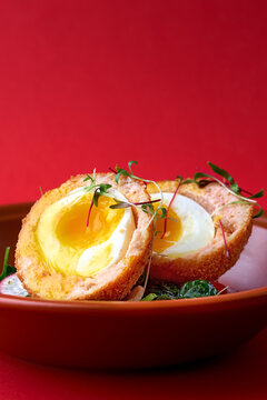 Typical British dish Scotch egg. red background.