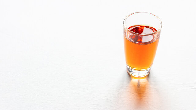 glass of alcohol on white background with place for text