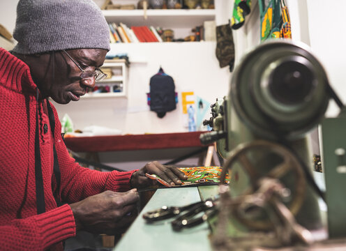 African man creating a bag with african background tissue while using sewing machine - Concept of craftwork