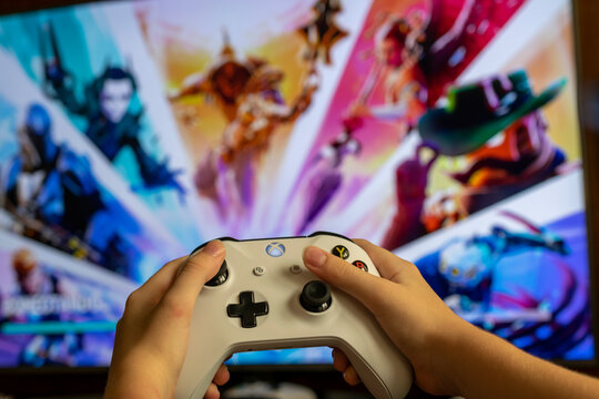 child with Xbox One video game controller, and in the background a blurred television panel with a Fortnite game screen. Selective focus.