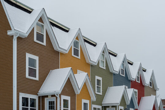 St. John's, Newfoundland, Canada - February 2021: Street View of multiple colourful row houses in downtown St. John's. The buildings have flat roofs, small windows, wood siding and multiple layers.