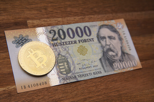Hungarian forint 20 000 forint banknote Ferenc Deák. Brown wooden table. Next to it is a gold bitcoin digital cryptocurrency coin. Bank image and photo.