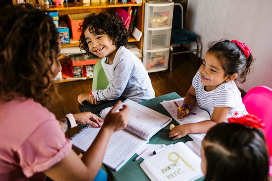 mexican children and mother at home in homeschooling concept in Mexico