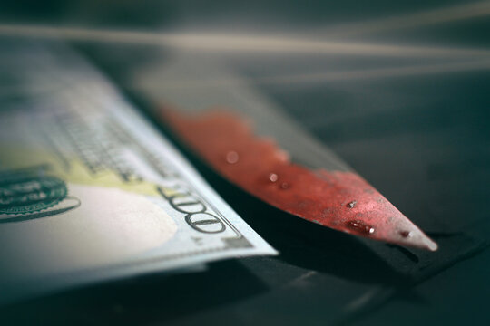 Blood on a knife blade, criminal world crime, murder, money, bloody knife horror theme, place for text close-up