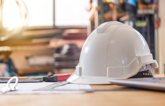 Construction concepts. White safety helmets blueprints on the engineering desks. Hard safety wear helmet hat on desks at construction site