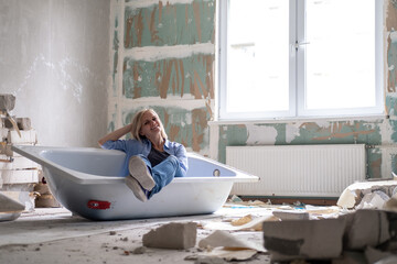 Obraz Renovation apartment. Creative story young happy woman sits in bathtub in the middle of the room. Empty walls, repairs house with their own hands. - fototapety do salonu