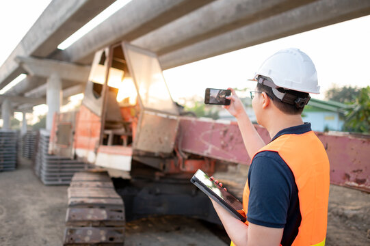 Smart Asian worker man or male civil engineer with protective safety helmet and reflective vest holding digital tablet using smartphone for taking photo of excavator machine at construction site.