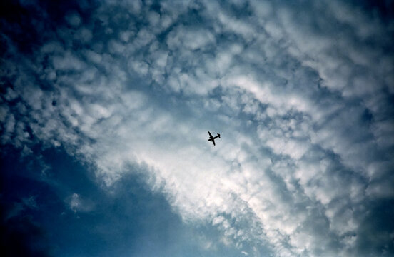 A dreamy view of a silhouetted antique airplane from below against sidelit shimmering white puffy clouds and a deep blue sky.