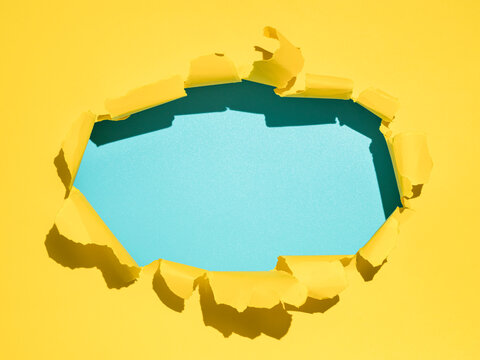 Torn bright yellow and blue empty paper background. Copy space. Yellow paper with oval hole with blank blue background inside for message, design or text. Hard light, sunny day.