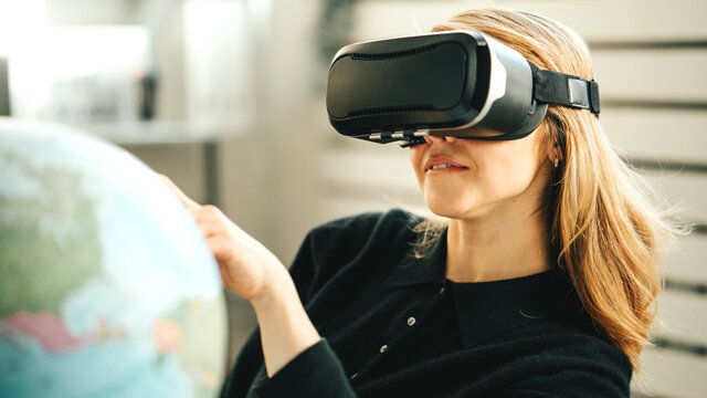 Pretty woman using vr headset and world map dreaming of travel to any destination while global lockdown