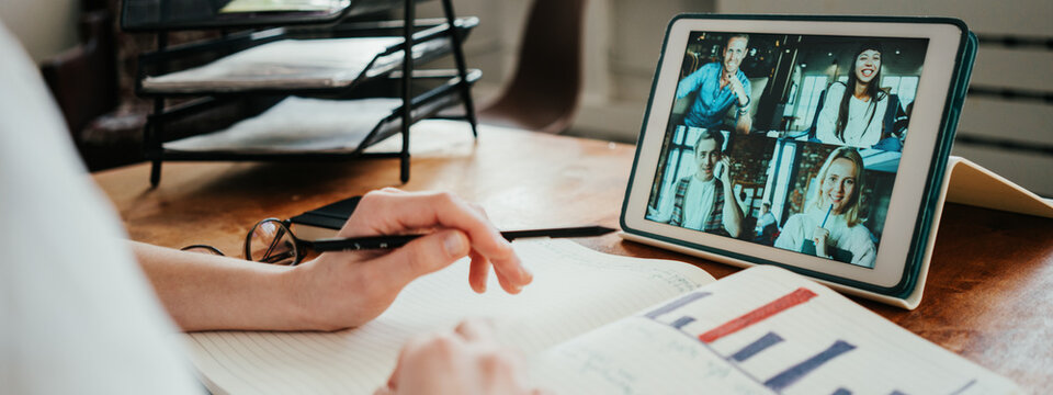 Woman has video conference call with her remote teammates using tablet computer. Note pad with stats and hands close-up