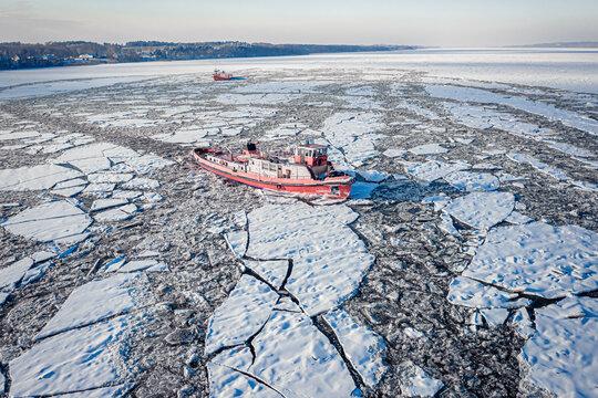 Icebreakers crushing ice on Vistula River in winter, Plock