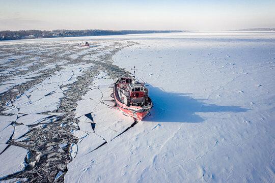 Icebreaker crushing ice on Vistula River in winter, Poland