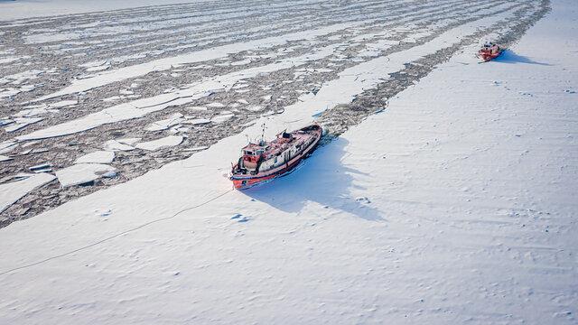 Two icebreakers on Vistula river crush the ice in winter