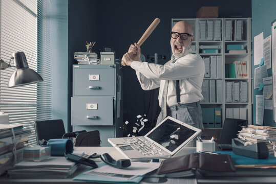 Crazy businessman destryoing his office with a baseball bat