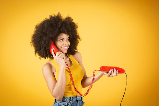 afro woman with an old cable phone, yellow background, red phone happy woman contented casual clothes