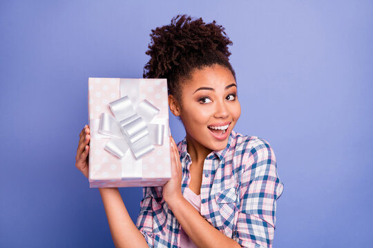 Photo of shiny adorable young lady dressed checkered shirt guess gift inside present box isolated purple color background