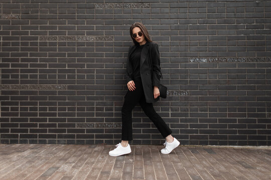 Pretty young stylish woman in fashionable black woolen clothes with a business blazer and white sneakers with a handbag walks near a black brick wall on the street
