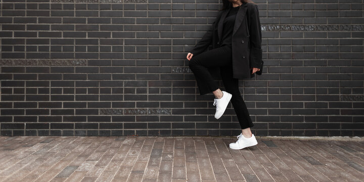 Cool girl in fashion denim pants in leather stylish sneakers in trendy jacket with black handbag standing on one leg near brick wall in city. Close-up female body. Fashionable casual youth womans wear