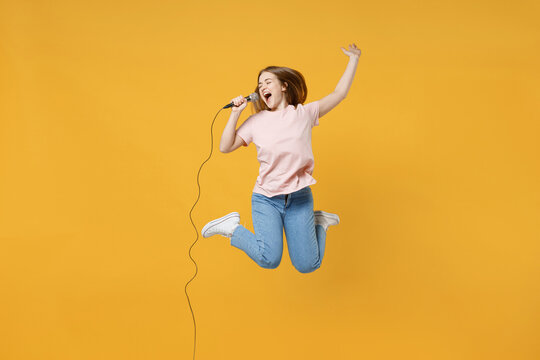 Full length of young expressive joyful singer woman 20s wearing casual basic pastel pink t-shirt jumping high singing song in microphone, karaoke isolated on yellow color background studio portrait.