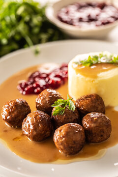 Plate serving Swedish meatballs kottbullar in sauce with mashed potatoes and cranberry sauce