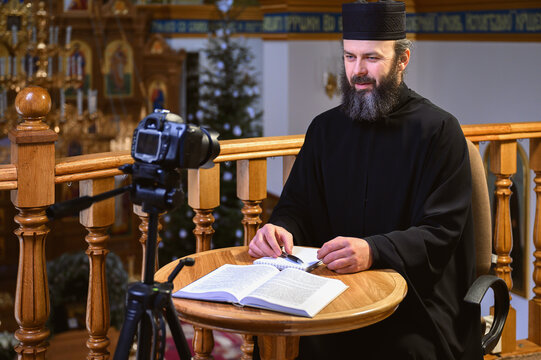 . An Orthodox priest is recording a video for his blog. Preaching during a pandemic.