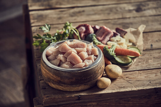 Meat in dog bowl near assorted vegetables on table