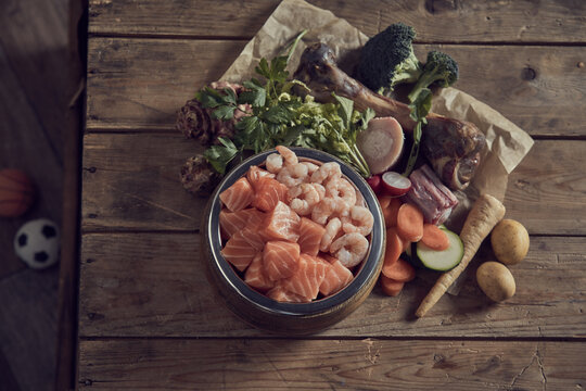 Bowl with seafood placed on table near cut ripe vegetables